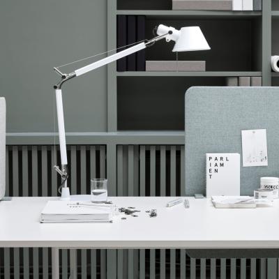 Lintex Edge lyddæmpende bordskærme monteret på hvidt skrivebord, hvor det står en hvid lampe og diverse skriveartikler.