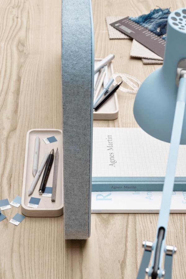 Close up billede set oppefra af en lyseblå Mood Fabric lydabsorberende bordskærm på stof på den ene side og skriveoverflade i glas på den anden side.