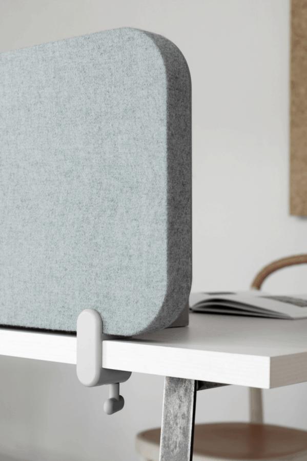 Close up billede af en Mood Fabric lydabsorberende bordskærm med blågrå stof på den ene side og glas på den anden side.