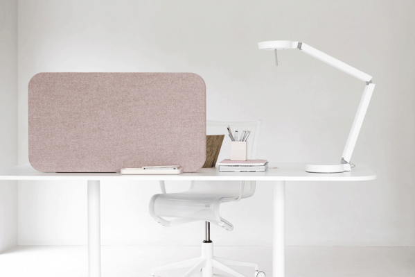 Meget lyst og klinisk skrivebord , hvorpå der står en rosa Mood Fabric bordskærm med stof på den ene side og magnetisk skriveoverflade i glas på den anden side.